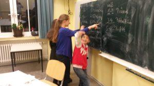 Kinder stehen an der Tafel und lernen deutsche Grammatik