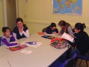 Mehrere Kinder sitzen an einem Tisch und lernen deutsch
