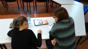 Mädchen sitzt mit Lehrerin am Tisch und erlernt die deutsche Sprache