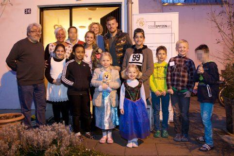 Timo und Carina Horn, eine Gruppe von Kindern, Betreuern und Mitgliedern des Domspitzen eV stehen vor der Jugendpädagogischen Einrichtung für ein Gruppenfoto. Im Hintergrund das DOMSPITZEN Logo.