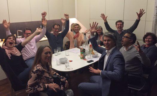 Mitglieder des DOMSPITZEN eV sitzen bei der Mitgliederhauptversammlung um einen Tisch herum, lachen und reißen die Arme in die Luft.