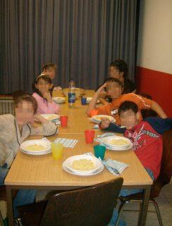 Flüchtlingskinder sitzen um einen Tisch, essen und machen Quatsch.