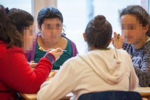 Kinder sitzen um einen Tisch, essen und diskutieren miteinander.