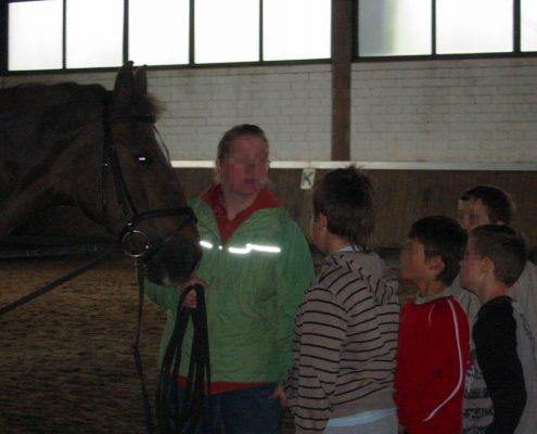 Eine Frau hält ein Pferd an einem Zügel und erklärt vier vor ihr stehenden Kindern, was sie zu beachten haben.