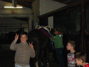 Ein Junge steht in einem Reitstall und macht das Victory-Zeichen, während im Hintergrund ein Pferd gesattelt wird.