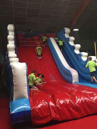 Kinder rutschen auf einer großen und breiten Indoor Rutsche
