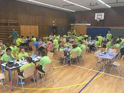 Alle Kinder der Tour essen gemeinsam in einer Turnhalle