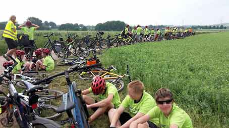 Radfahrer mit und ohne Behinderung machen eine Pause am Wegrand