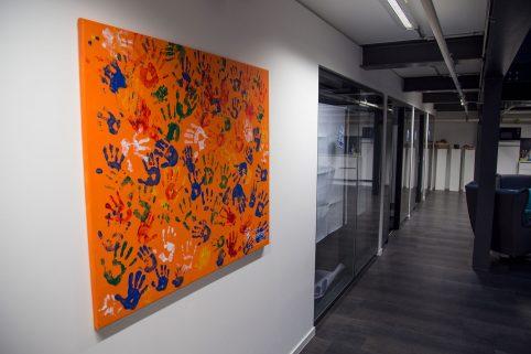 Ein Bild (orangener Hintergrund mit bunten abdrücken von Kinderhänden) hängt im Büro der Agentur Wunderman. Domspitzen eV.