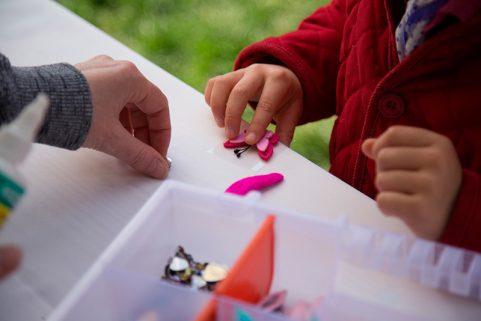 Eine kleine Kinderhand bastelt Spängchen am Stand des Domspitzen eV beim Weltkindertag.