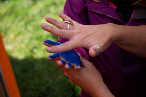Ein Kind bekommt mit blauer Farbe seine Hand bemalt, um sie auf die Leinwand des Domspitzen eV zu drücken.