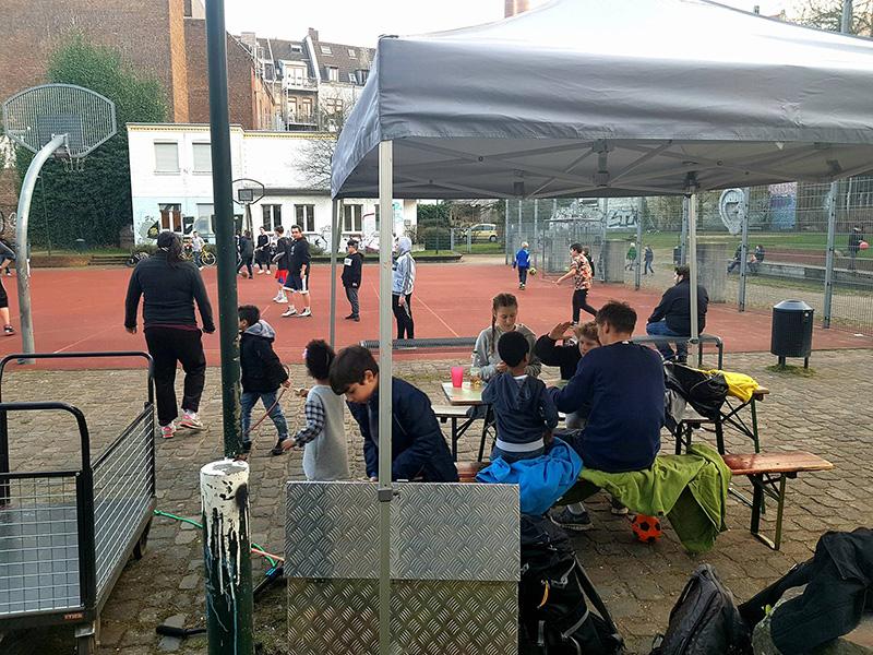 Im Hintergrund spielen Kinder mit und ohne Fluchthintergrund gemeinsam Basketball. Vorne ein Pavillon, unter dem Kinder und Betreuer eine Pause machen.