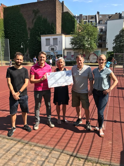 5 Personen stehen auf einem Basketballplatz und schauen in die Kamera. Josi Dörflinger vom Domspitzen eV hält einen großen Scheck in der Hand.