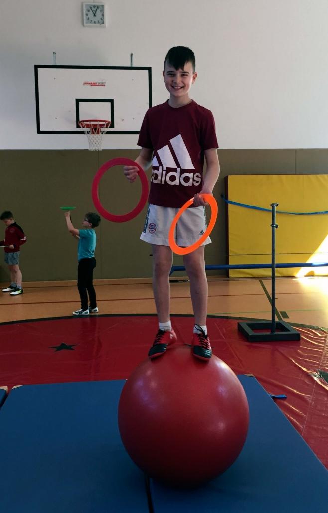 Zirkustraining an der Eduard-Mörike-Schule. Ein kleiner Junge balanciert auf einer Kugel und jongliert dabei.