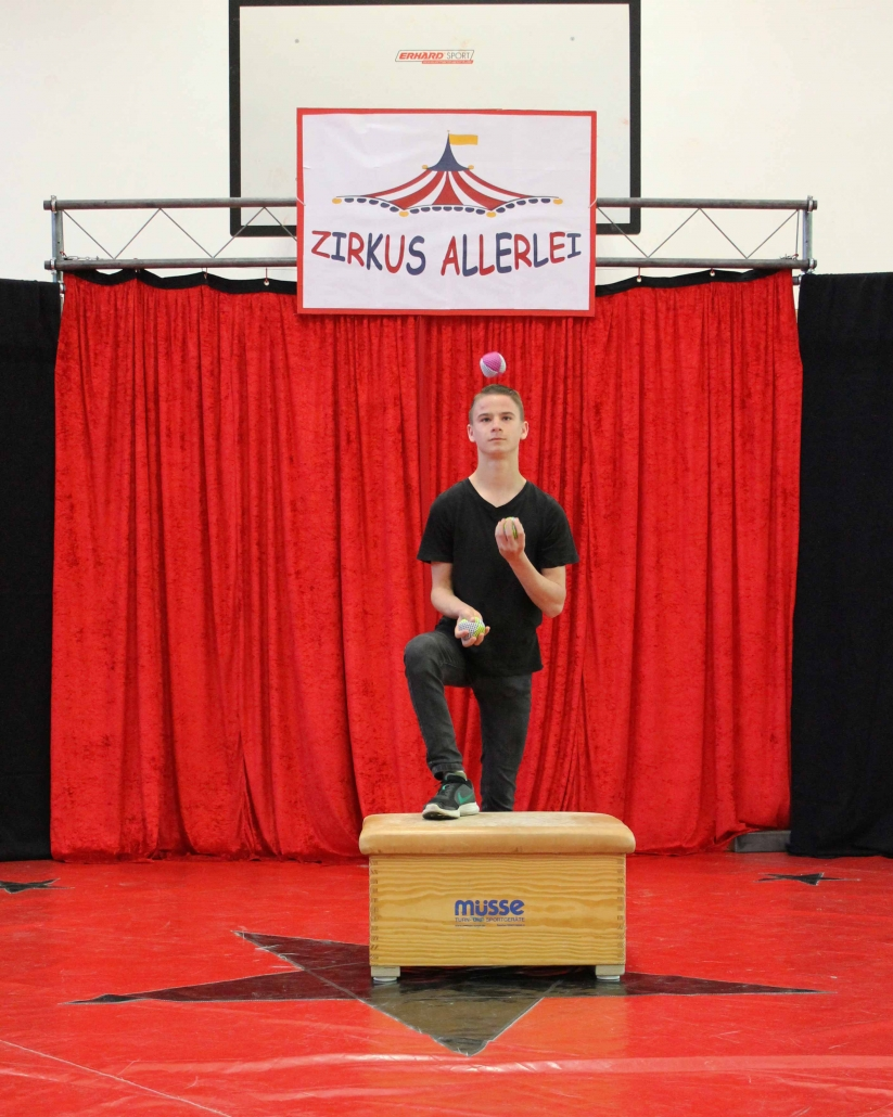 Zirkustraining an der Eduard-Mörike-Schule. Ein Junge steht mit einem Bein auf einem Kasten und jongliert mit Bällen.