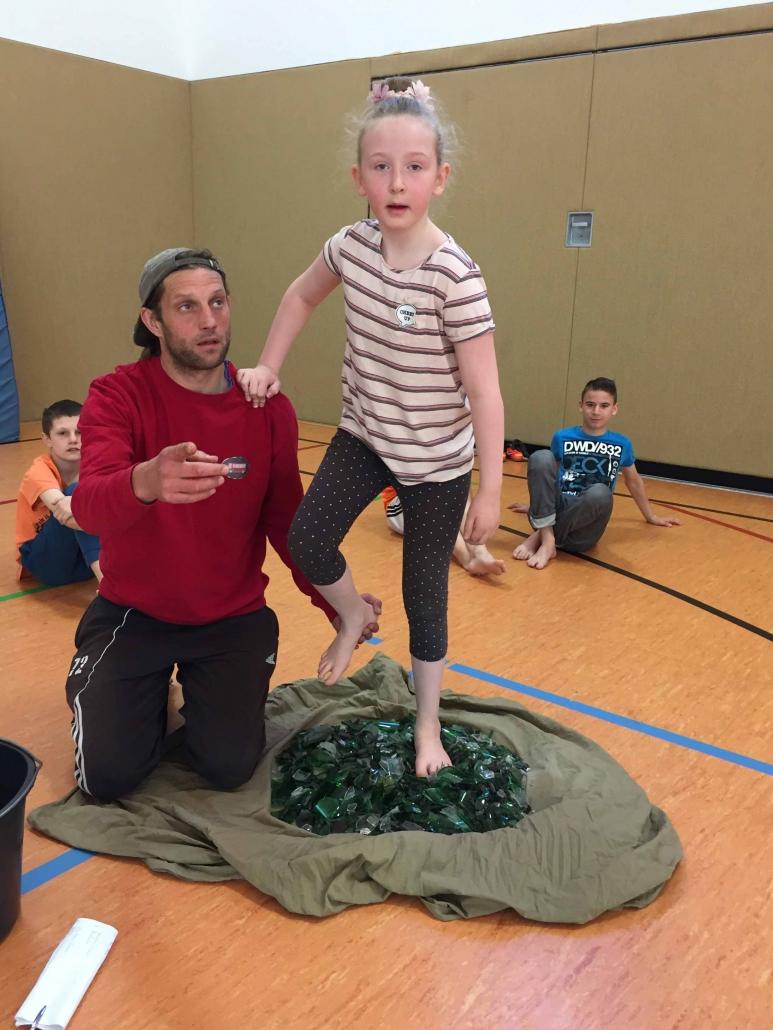 Zirkustraining an der Eduard-Mörike-Schule. Ein Mädchen steht in einem Haufen mit Scherben auf einem Bein. Ein Trainer stützt sie am anderen Bein.