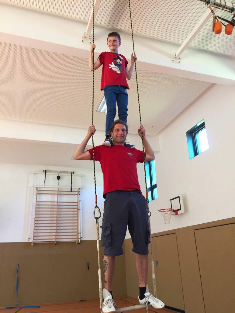 Zirkustraining an der Eduard-Mörike-Schule. Ein Mann steht auf einem Trapez. Auf einen Schultern steht ein kleiner Junge.